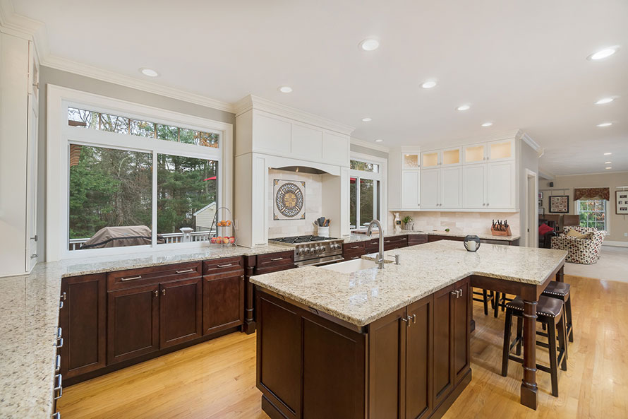 Light floors contrasting dark cabinets in a kitchen. Has two large windows on either side of a large stove and decorative tiled back splash with a molding trimmed hood.