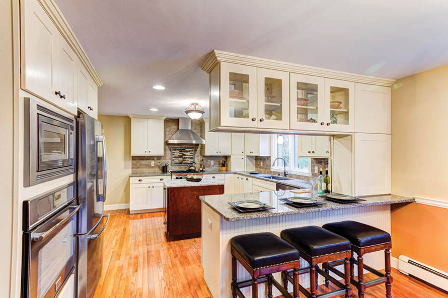 A kitchen with off-white to cream cabinets in a U with hardwood floors.